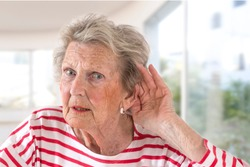 Elderly lady with hearing problems due to ageing holding her hand to her ear as she struggles to hear, profile view on windowns background