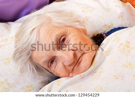 Elderly lonely woman in the bed
