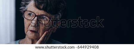 Elderly lonely woman with Alzheimer's sadly looking through the window