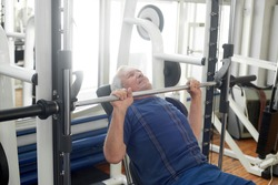Elderly male is having intense workout in gym. Senior caucasian man lifting weights at fitness club. Strength workout for seniors.