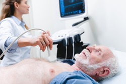 Elderly male patient undergoing examination chest by female doctor with ultrasonography device