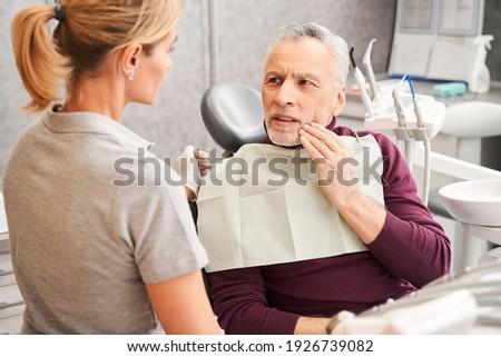 Elderly male patient with toothache talking to his dentist at the clinic. Man suffering of the pain. Aching, inflammation, infection, painful, helping and treatment concept Stock photo ©