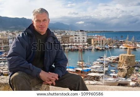 elderly man against the port of Kyrenia