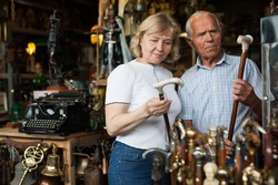 Elderly man and woman examine rare walking stick on flea market. High quality photo