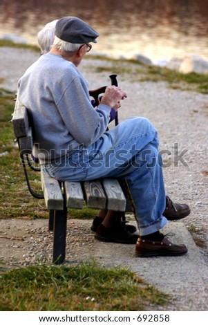 Elderly man and woman sitting on park bench