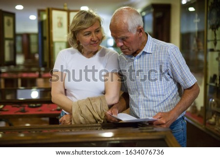 Elderly man and woman visiting historical museum and looking at showcases with exhibits