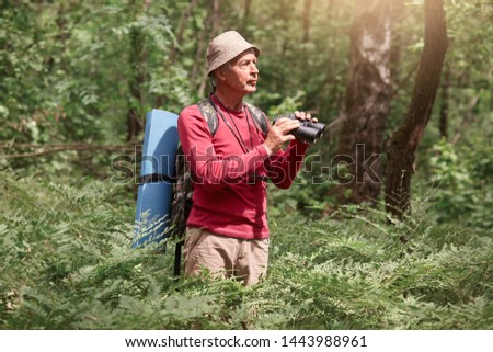 Elderly man birdwatching while standing outdoors in forest, scanning his surroundings with binoculars, male dressed casual red sweater and cap, posing with backpack and rug, enjoying beautiful natue.