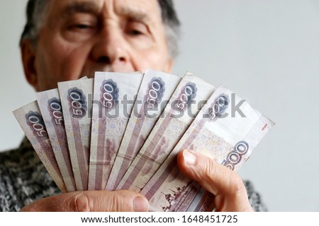 Elderly man counts russian rubles in hands. Pension payments, retirement savings or benefits concept, male pensioner with paper currency of Russia
