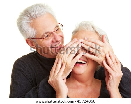 Elderly man covering the eyes of his wife