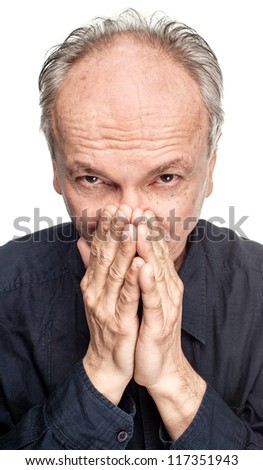 Elderly man covers his face with hand