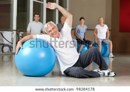 Elderly man doing back exercises with gym ball in fitness center