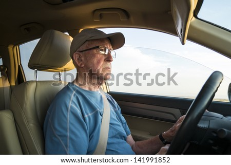 Elderly man driving a car with seat belt on