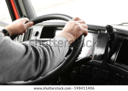 Elderly man driving big modern truck, closeup