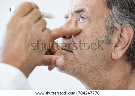 Elderly man examined by an ophthalmologist #704247778