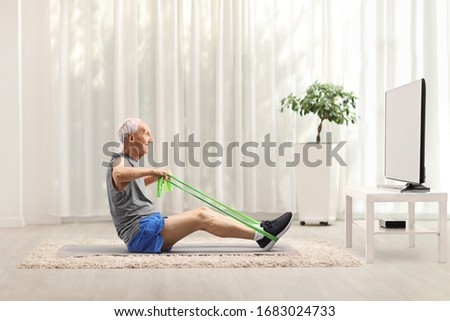 Elderly man exercising with an elastic band in front of a tv at home