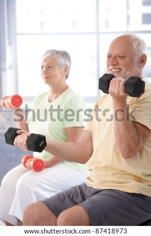 Elderly man exercising with dumbbells at gym.?