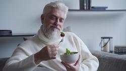 Elderly man feel happy enjoy eating diet food fresh salad on sofa