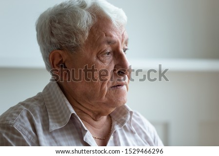 Elderly man feels sad and lonely looks away close up face, grey haired 70s grandfather thinking about disease or recollect life in nursing home care, concept of medicine for seniors, medical insurance