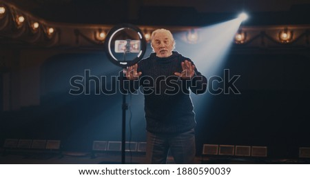 Elderly man gesticulating and talking while recording acting lesson on in spotlight on stage in theater Stockfoto ©