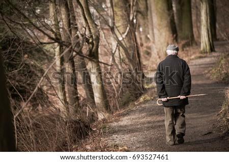 Shutterstock Elderly man going away in park. Toned