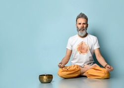 Elderly man, Hare Krishna follower, dressed in traditional orange and white dhoti clothes, holding rosary, sitting on floor in lotus pose on blue background. Singing bowl nearby. Close up, copy space
