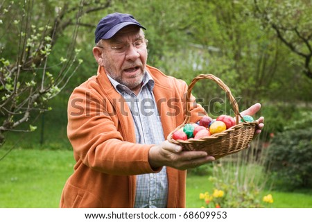 Elderly man holding basket of Easter eggs