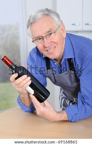 Elderly man holding bottle of red wine
