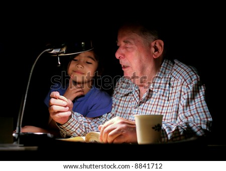Elderly man holding coin and talking to granddaughter by lamplight, dark shadows in background.