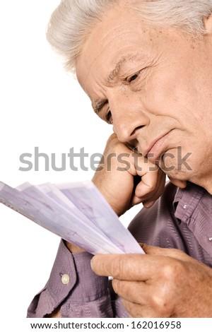 Elderly man holding euros isolated on white background