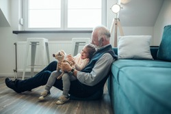 Elderly man holding his granddaughter