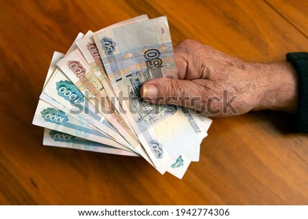 Elderly man holding russian ruble banknotes in hand. The concept of pension, payment and money savings.