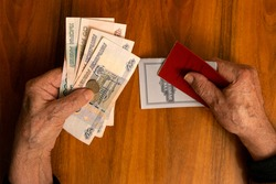 Elderly man holding russian ruble banknotes in one hand and pension certificate with passbook in another. The concept of pension, payment and money savings.