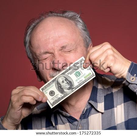 Elderly man holding with pleasure one hundred dollar bill