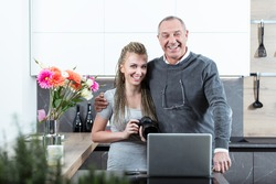 Elderly man hugging beautiful young woman with DSLR camera, like father and daughter, posing at camera and laughing, standing in the kitchen at home with laptop on table