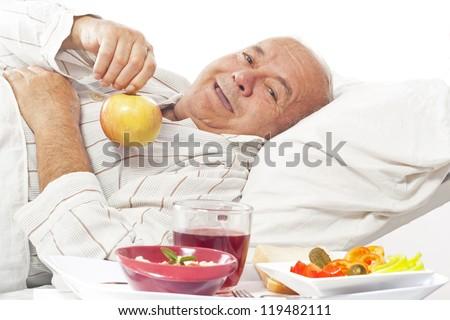 elderly man in a hospital bed eating