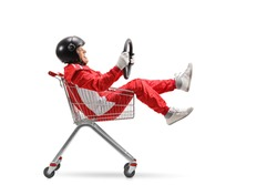 Elderly man in a racing suit with helmet holding a steering wheel and sitting inside a shopping cart isolated on white background