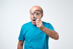Elderly man in blue t-shirt looking through a magnifying glass. Concept of quality control checking. Let me see all the benefits