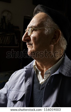 Elderly man in cap and eyeglasses sideview in darkness