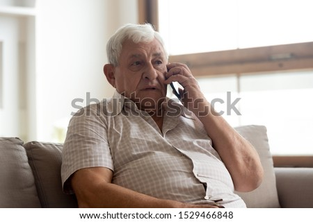 Elderly man in casual clothes seated on couch in living room holding mobile phone talking having distant communication with doctor getting services or recommendations from therapist counsellor concept