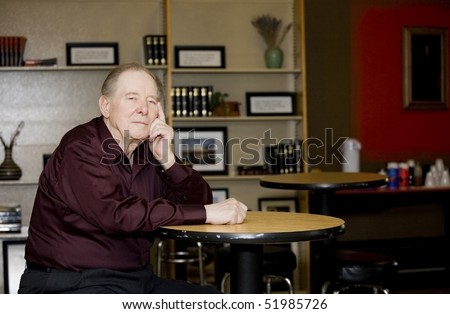 Elderly man in coffee shop, sitting alone at a table
