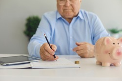 Elderly man in shirt in glasses sitting with calculator and piggybank for savings and making notes about saving pension in room interior, selective focus. Small pension, saving money, budget concept