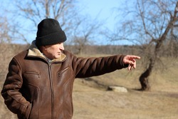 Elderly man in warm clothes points to something in the distance. Rural scene, concept of old age, life in village