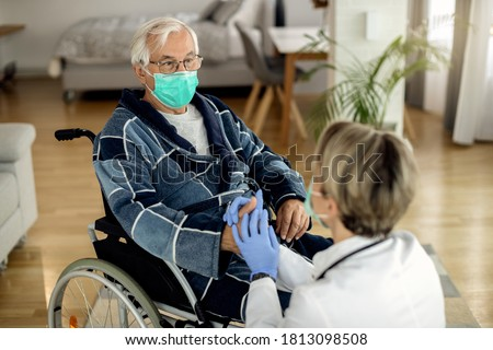 Elderly man in wheelchair communicating with a doctor while holding hands with her at home. Both of them are wearing protective face masks due to COVID-19 epidemic.