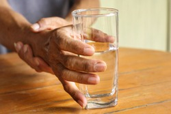 Elderly man is holding his hand while drinking water because Parkinson's disease.Tremor is most symptom and make a trouble for doing activities such as eat or drink.Health care or elderly concept.