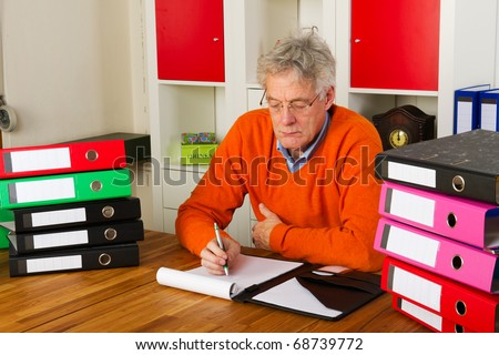 Elderly man is sitting with many paper folders and writing a letter