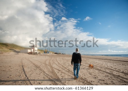 Elderly man is walking his dog at the beach