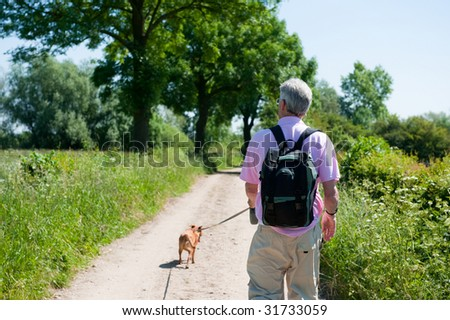 Elderly man is walking with his dog in nature