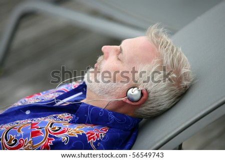Elderly man laid on a deck chair listening to music