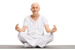Elderly man meditating on an exercise mat isolated on white background