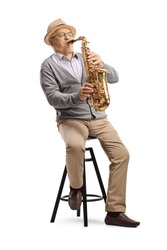 Elderly man musician playing a sax and sitting on a chair isolated on white background